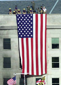 September 11, 2001 - Firefighters drape a giant American flag over the exterior of the Pentagon, next to the gaping smoking hole left by the impact of the hijacked plane, so that as television cameras reported from the scene, Americans as well as the terrorists responsible would be reminded of America's strength, determination, and resiliency.