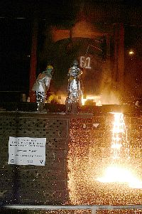 Molten steel salvaged from the World Trade Center is poured into a mold to form the bow stem of USS New York (LPD-21)