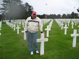 After 64 years, Bill Knudsen finally meets his father, Bill Cuthbert, at the latter's grave in the American cemetery in Normandy.