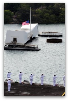 Sailors and officers render honors as their ship passes the USS Arizona Memorial in Pearl Harbor, Hawaii.